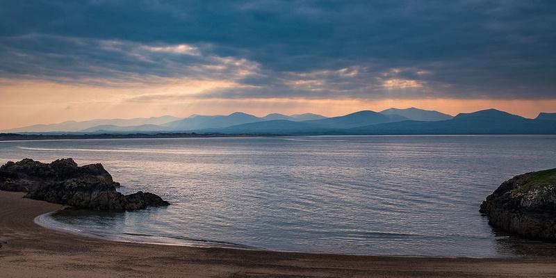 Snowdonia mountains sunrise from Llanddwyn Island Anglesey